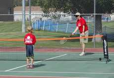 child playing tennis with instructor